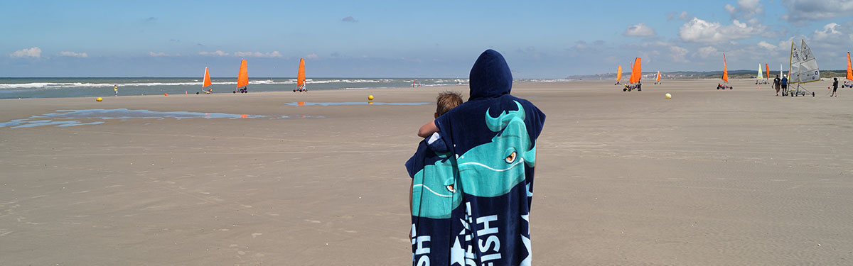 2 kids wearing changing towels looking out to sea on the beach